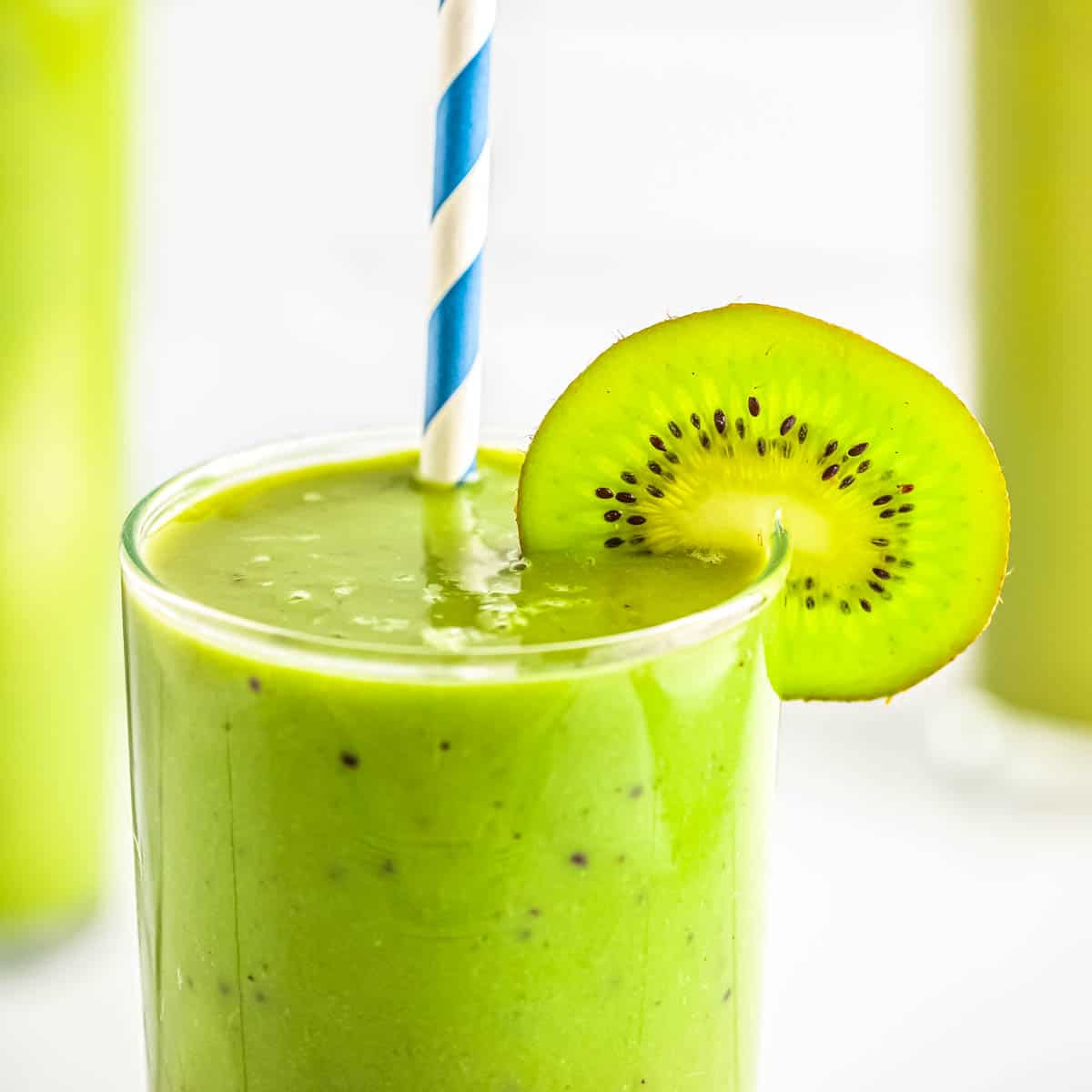 Close up shot of matcha green tea smoothie in a clear glass with a slice of kiwi and a straw with a white and green background.