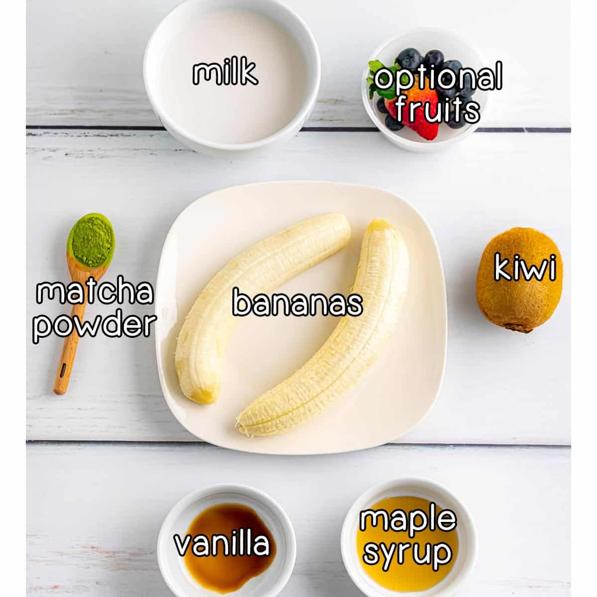 Overhead shot of ingredients- bananas, milk, fruits, kiwi, maple syrup, vanilla, and match powder.