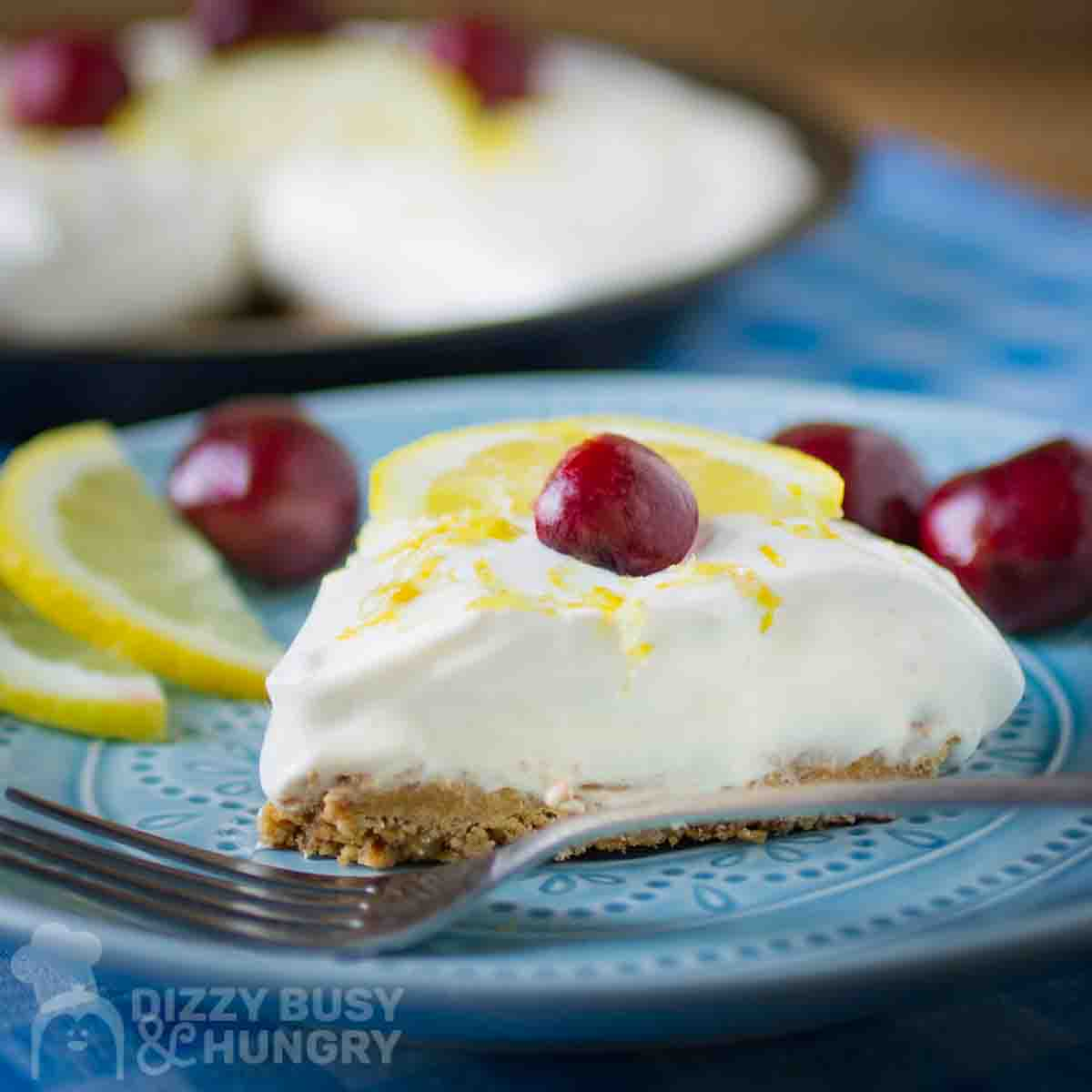 Side close up shot of a slice of lemon pie garnished with a whole cherry on a blue plate with a fork, lemon slices, and more cherries on the side.