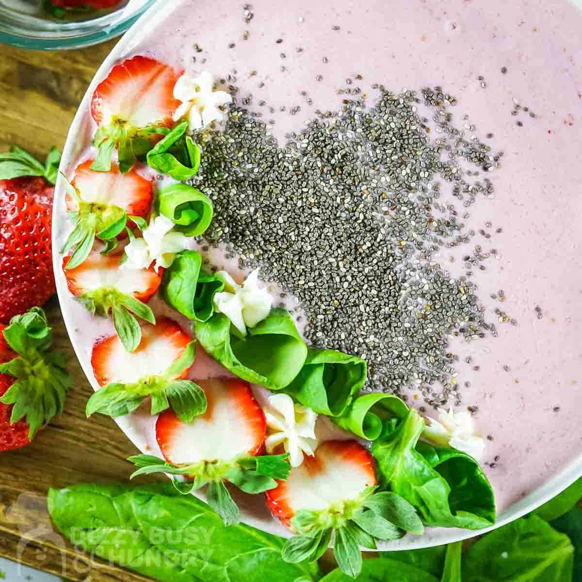 Overhead shot of pink smoothie bowl garnished with flax seeds, sliced strawberries, and mint rolls on a wooden surface with more mint and strawberries on the side.