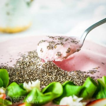 Side close up shot of a spoon in a smoothie bowl garnished with flax seeds, mint, and sliced strawberries on a wooden surface with more mint on the side.