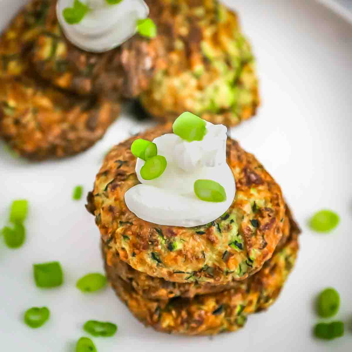 Overhead view of three zucchini fritters stacked on each other with a dollop of sour cream and green onions sprinkled on a white plate.