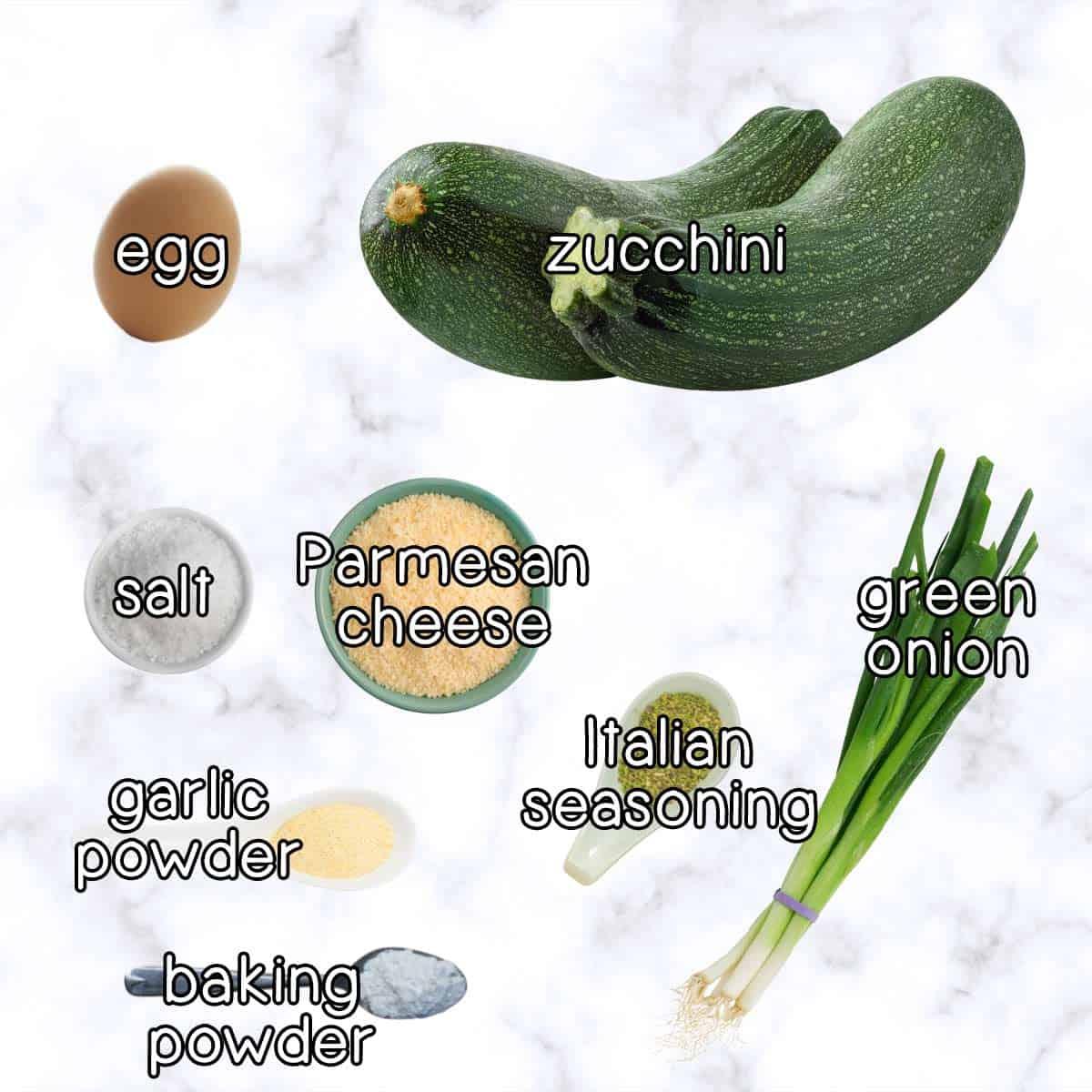 Overhead shot of ingredients- zucchini, an egg, salt, parmesan cheese, garlic powder, baking powder, Italian seasoning, and green onion.