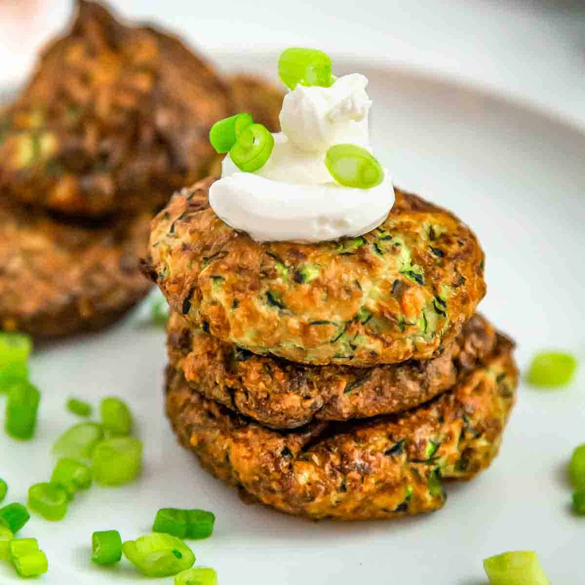 Side shot of three zucchini fritters stacked on each other with a dollop of sour cream and green onions sprinkled on a white plate.