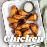 Chicken wings with dipping sauce on a plate.
