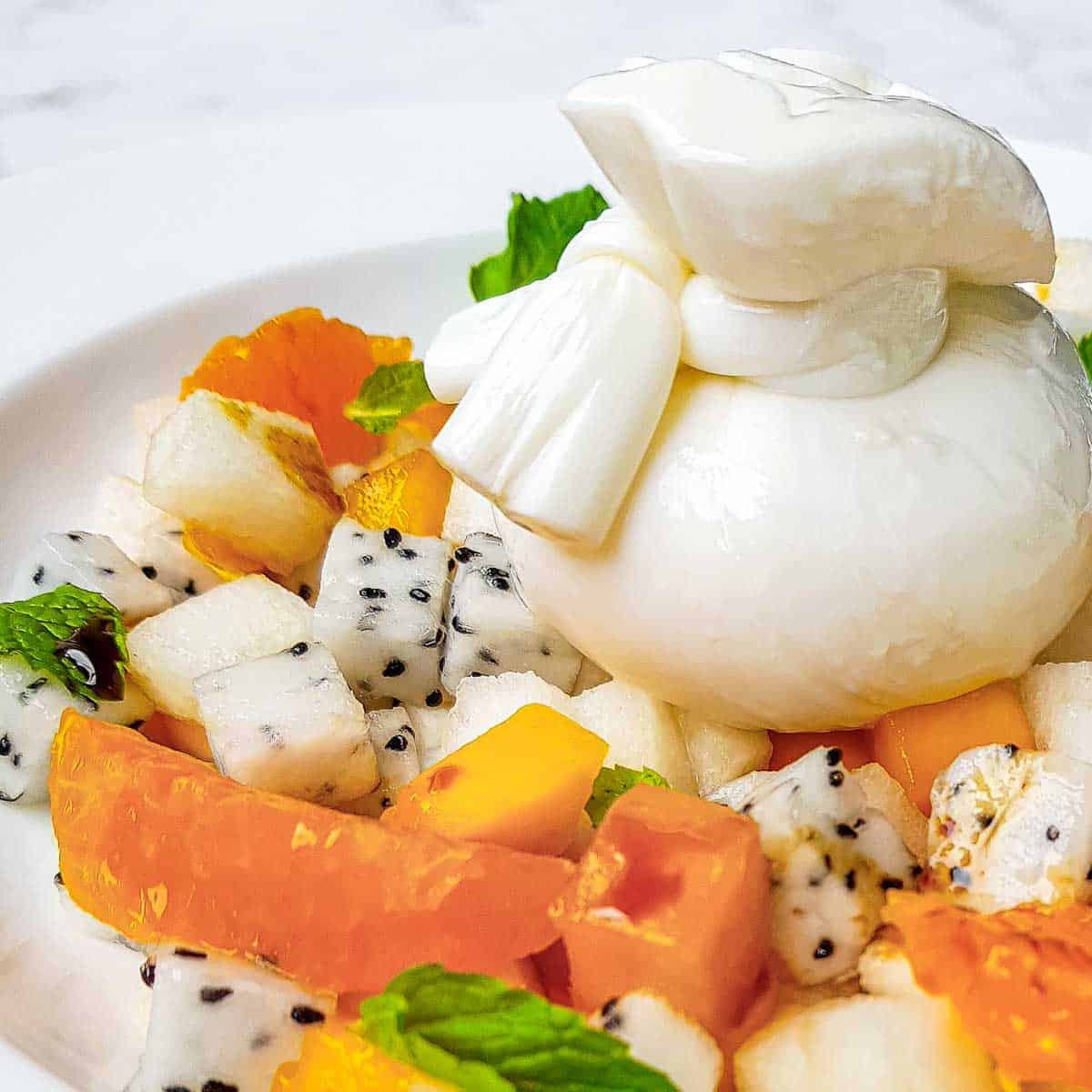 Side close up shot of colorful burrata salad garnished with mint in a white bowl on a marble table.