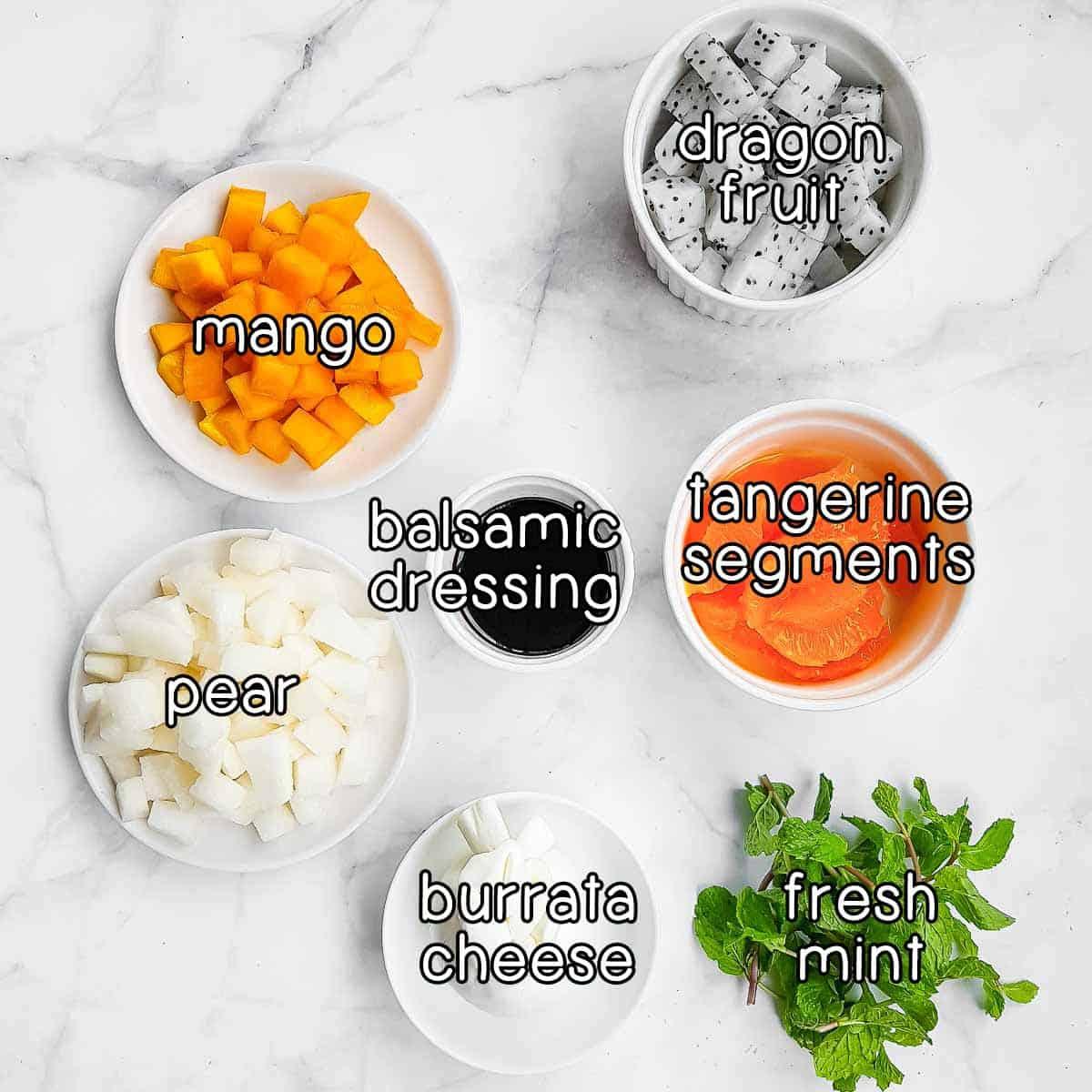 Overhead shot of ingredients- mango, dragon fruit, tangerine segments, pear, balsamic dressing, burrata cheese, and fresh mint.