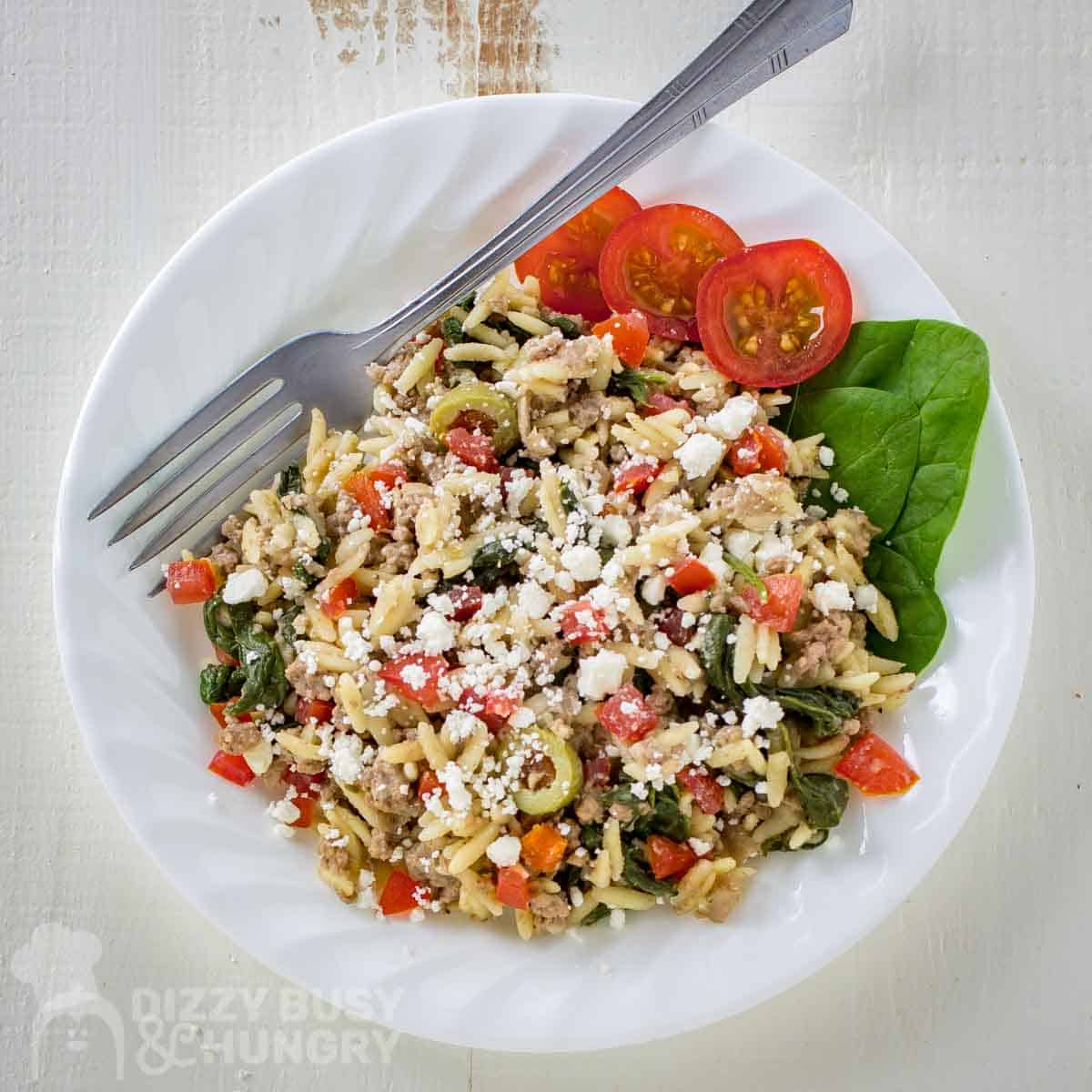 Overhead shot of ground beef orzo pasta in a white bowl with sliced tomatoes, spinach and a fork on the side.