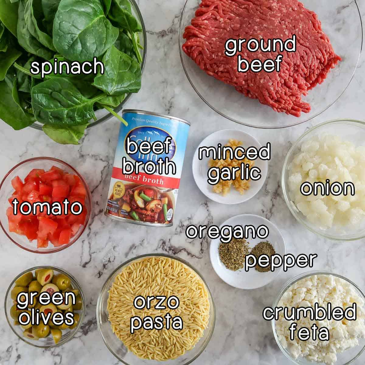 Overhead shot of ingredients- spinach, ground beef, tomato, beef broth, minced garlic, onion, green olives, orzo pasta, oregano, pepper, and crumbled feta.