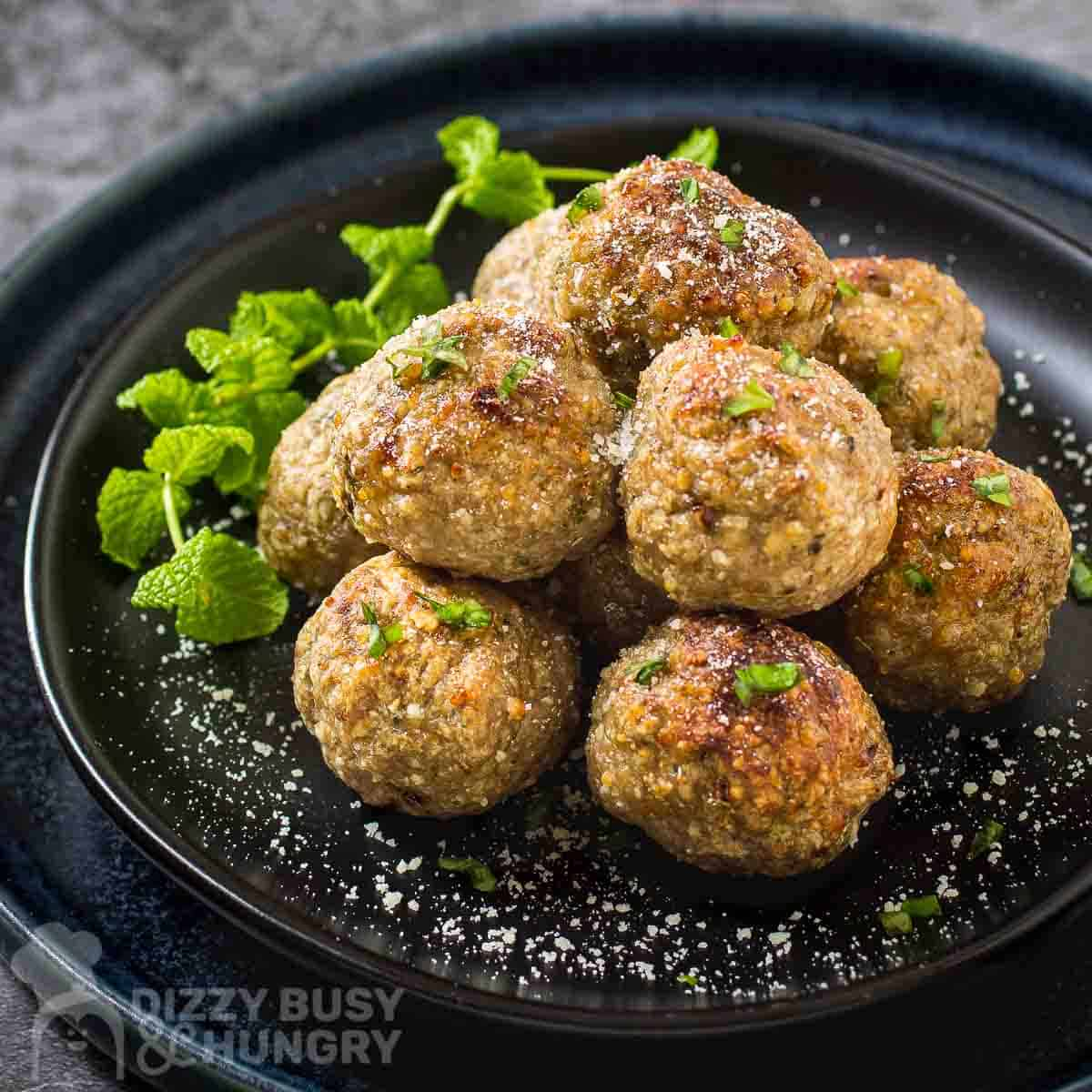 Side shot of multiple meatballs stacked on a black plate garnished with herbs and parmesan cheese.