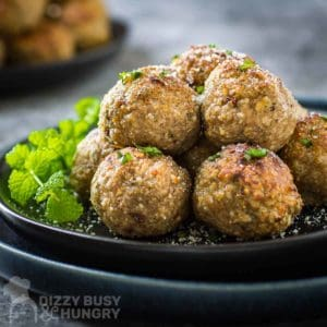 Side shot of multiple meatballs stacked on a black plate garnished with herbs and parmesan cheese with more meatballs in the background.
