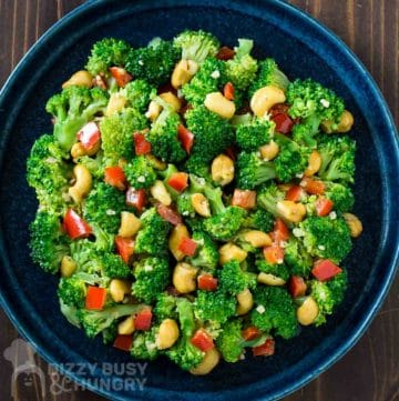 Overhead shot of garlic butter broccoli in a blue bowl on a wooden surface