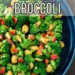 Overhead close up shot of garlic butter broccoli in a blue bowl on a wooden surface