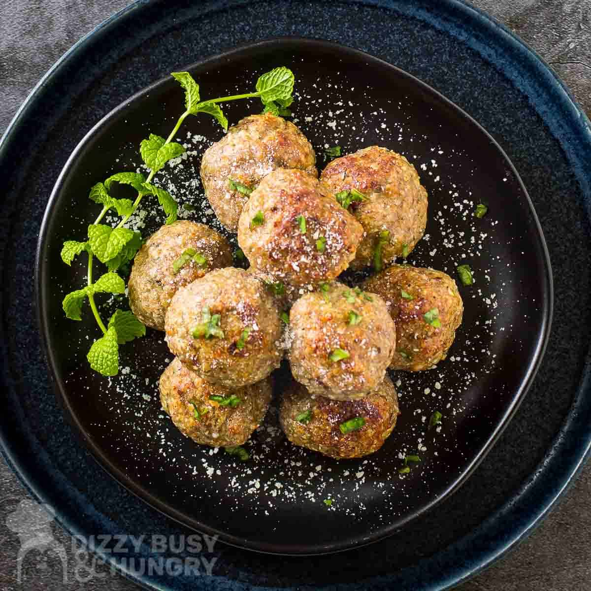 Overhead shot of multiple meatballs stacked on a black plate garnished with herbs and parmesan cheese.