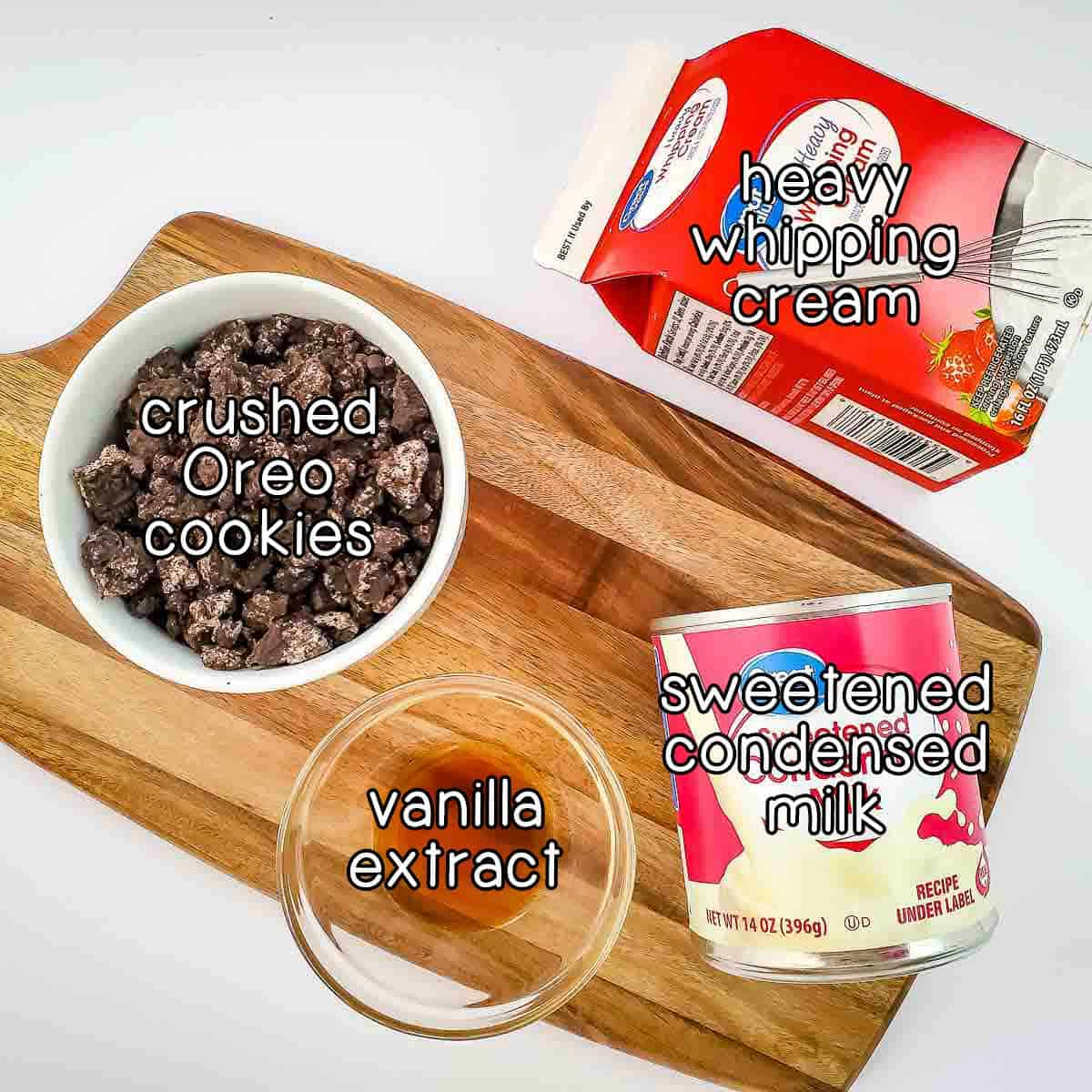 Overhead shot of ingredients- crushed Oreo cookies, heavy whipping cream, sweetened condensed milk, and vanilla extract on a wooden cutting board.