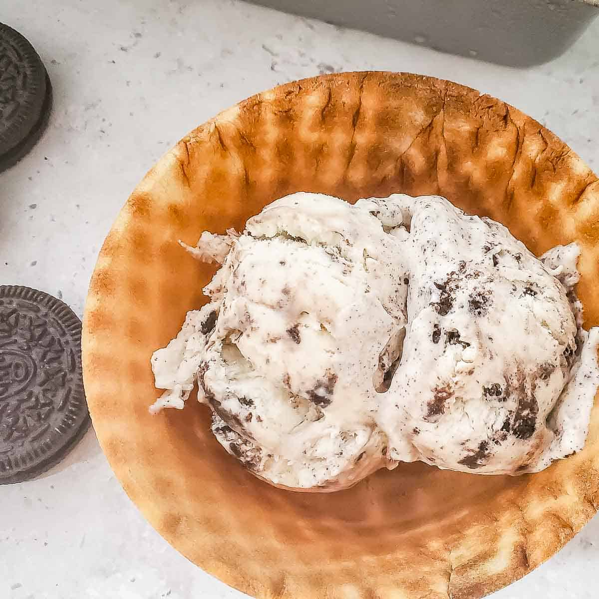 Overhead close up shot of ice cream in a waffle cone bowl on a white marble surface with Oreos and a metal pan in the background.