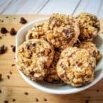Side shot of multiple energy balls in a white bowl on a cutting board sprinkled with flax seeds and chocolate chips.