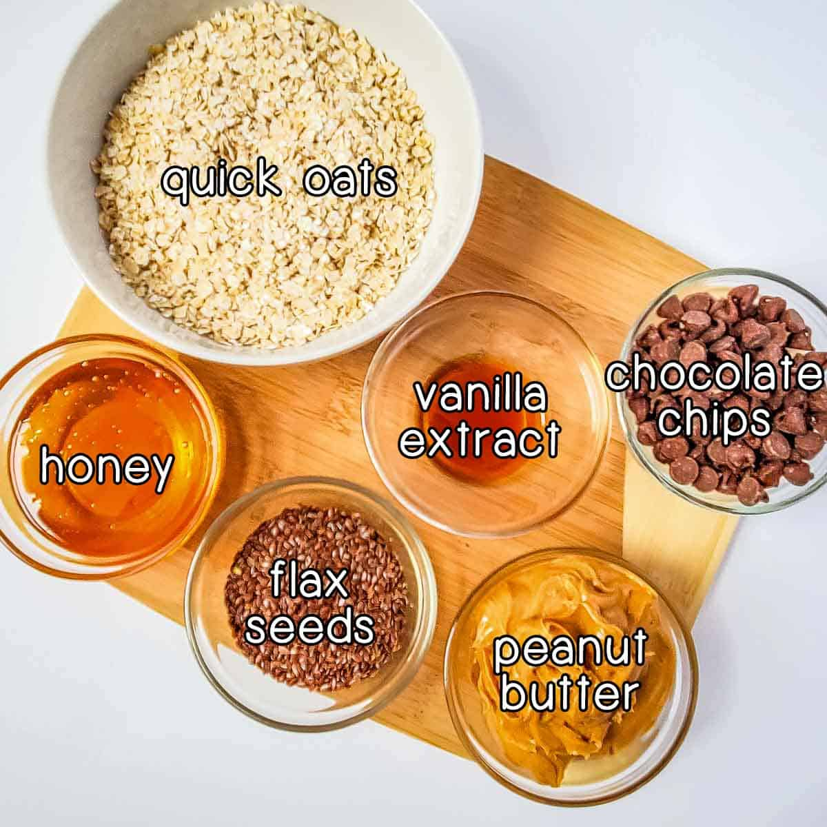 Overhead shot of ingredients laid out on a cutting board- quick oats, vanilla extract, chocolate chips, peanut butter, flax seeds, and honey.