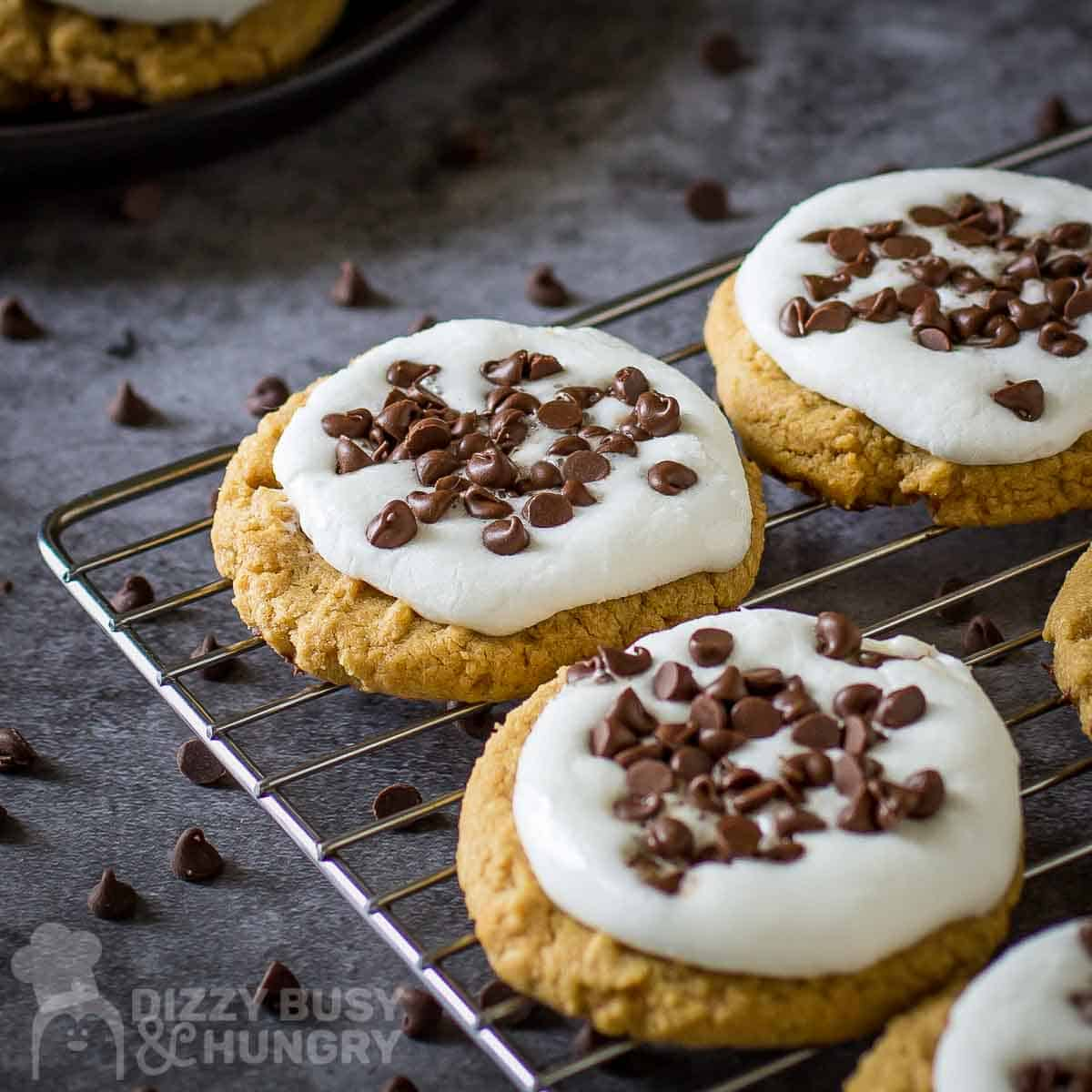Close up side shot of multiple smores cookies on a wire cooling rack on a grey surface with chocolate chips scattered around.