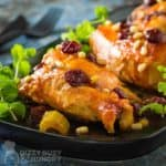 Side shot of three pieces of cranberry chicken garnished with cranberries and herbs on a black plate with cutlery in the background.