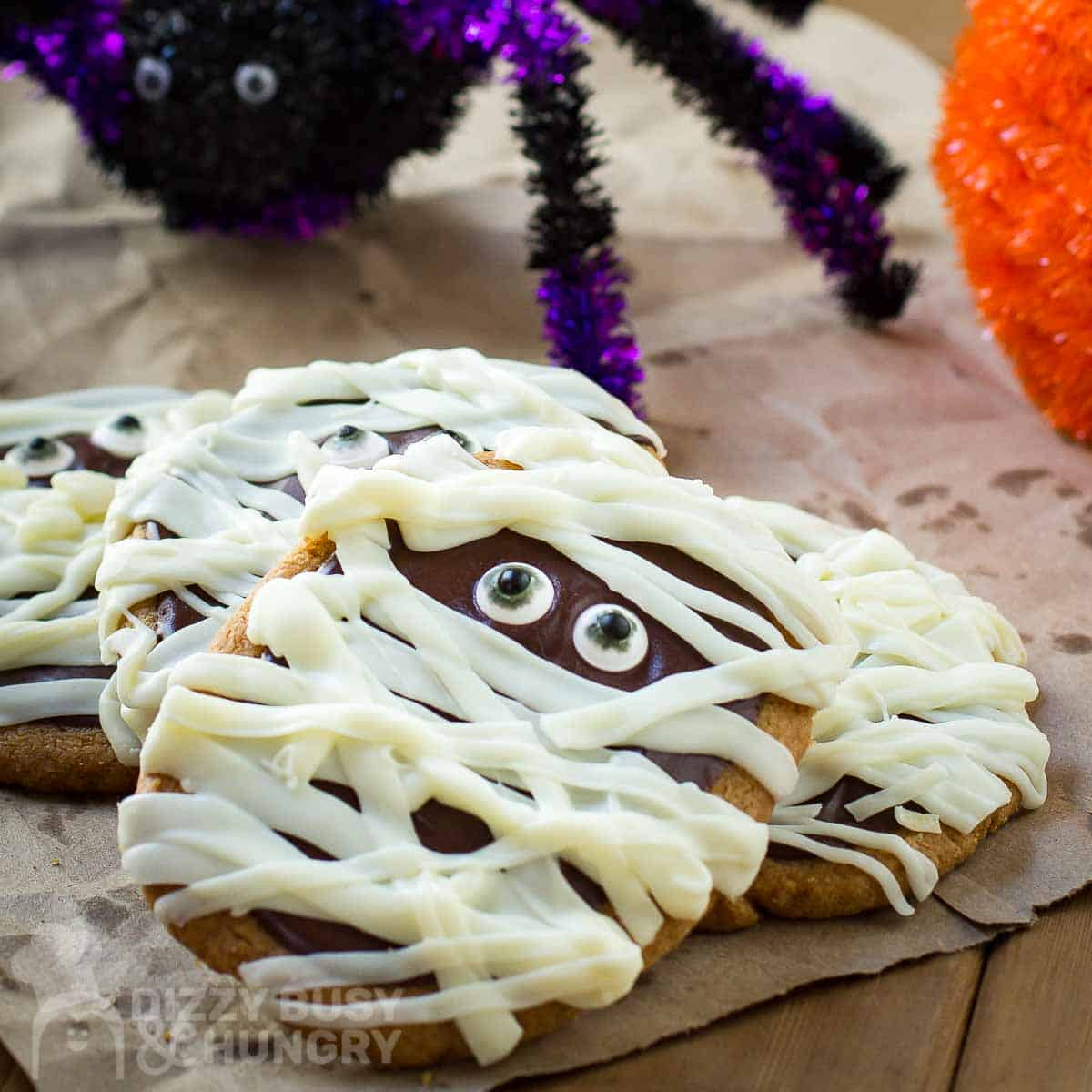 Close up shot of multiple mummy cookies stacked on each other with a purple and black decorative spider in the background.