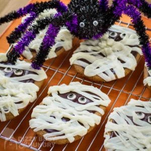 Side angled view of multiple mummy cookies on a cooling rack with a purple and black decorative spider in the background.