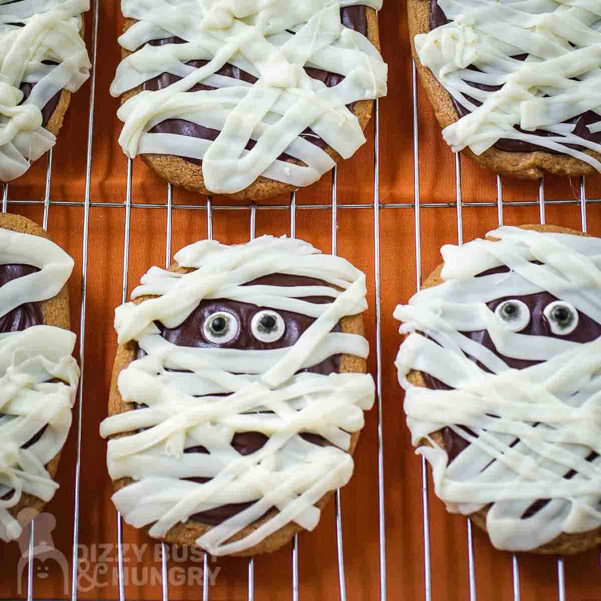 Overhead shot of multiple mummy cookies on a cooling rack on an orange surface.