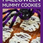 Side shot of multiple mummy cookies on a cooling rack with a purple and black decorative spider in the background.