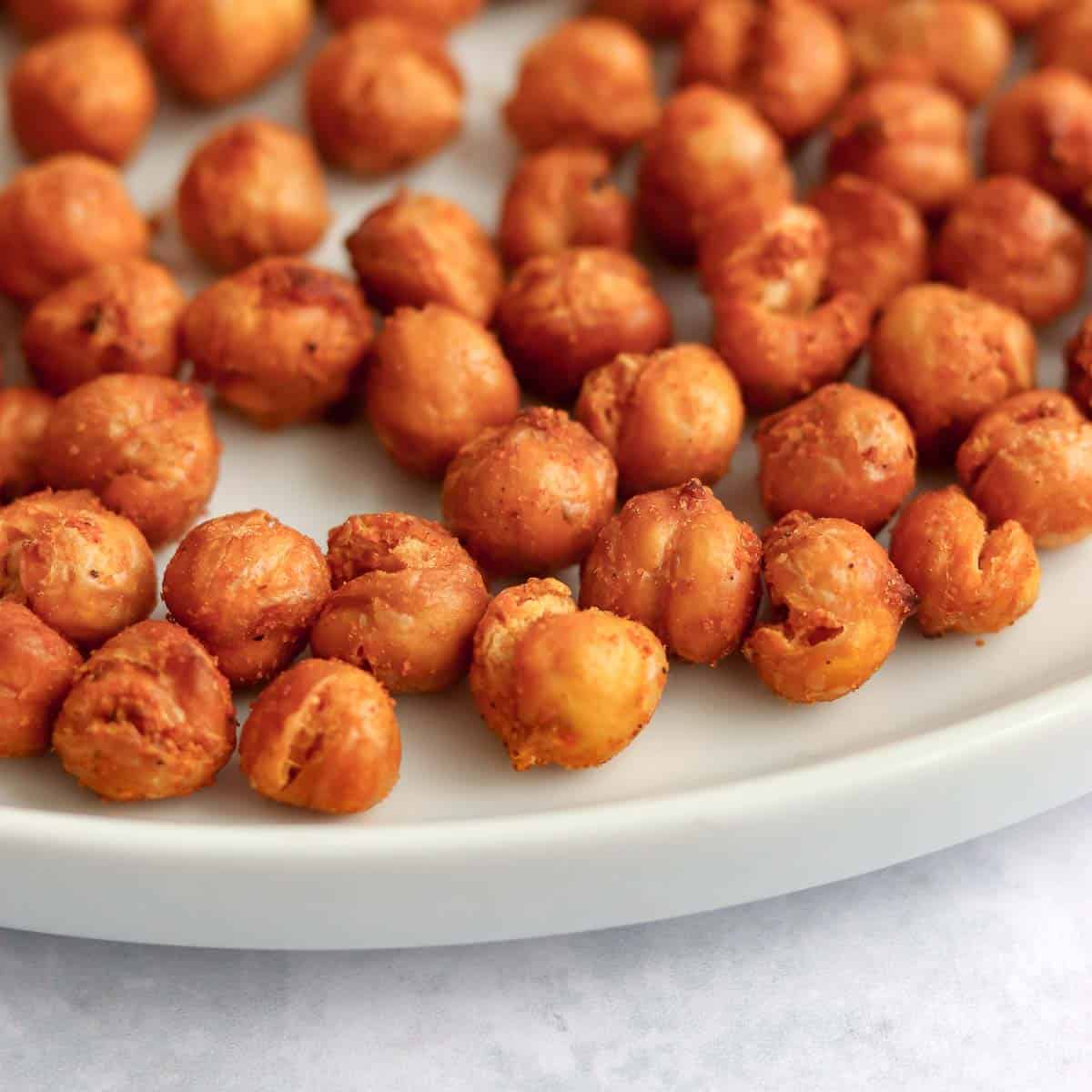 Close up side view of crispy chickpeas on a white plate on a marble surface.