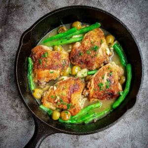 Overhead shot of pan fried chicken thighs with olives and green beans in a skillet on a black surface.