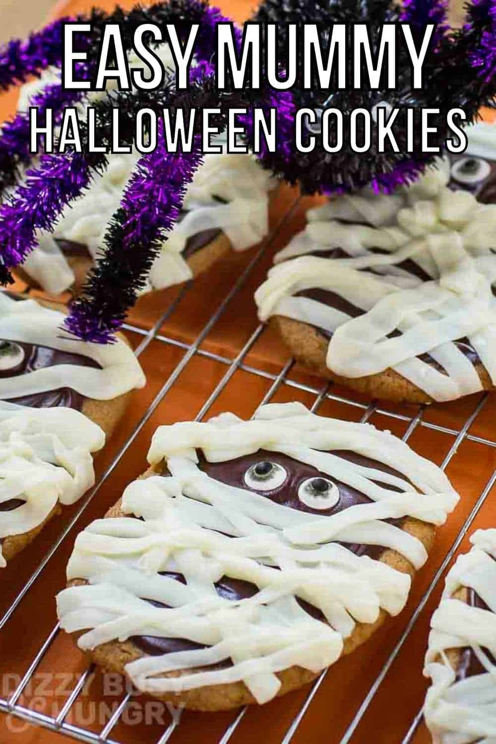 Side close up shot of multiple mummy cookies on a cooling rack with a purple and black decorative spider in the background.