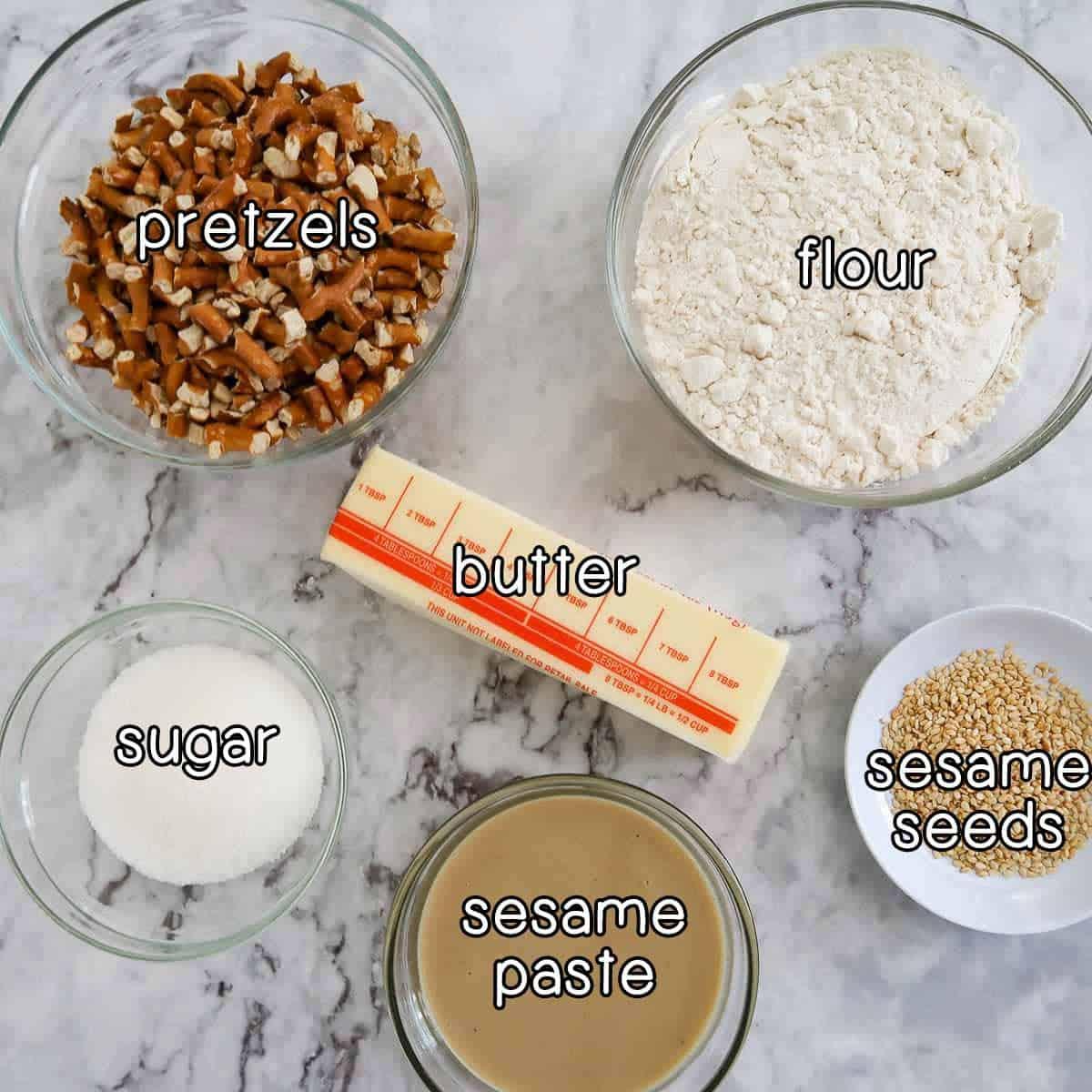 Overhead shot of ingredients- pretzels, flour, butter, sugar, sesame paste, and sesame seeds.
