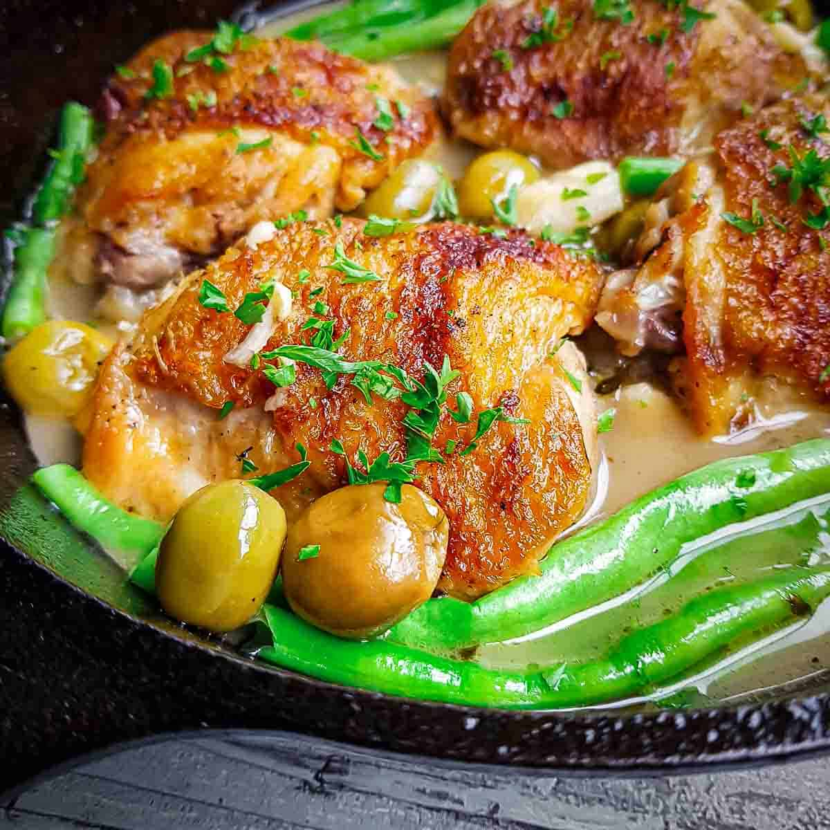 Close up angled view of pan fried chicken thighs with olives and green beans in a skillet on a black surface.