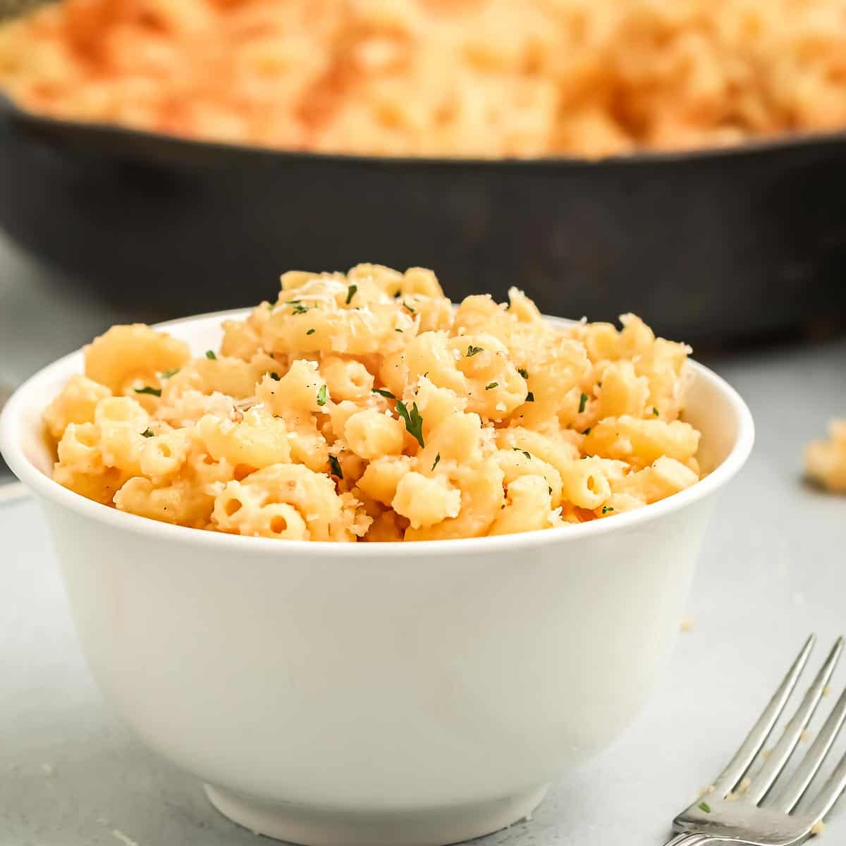 Side shot of Mac and cheese in a white bowl with a fork on the side and a skillet with more Mac and cheese in the background.