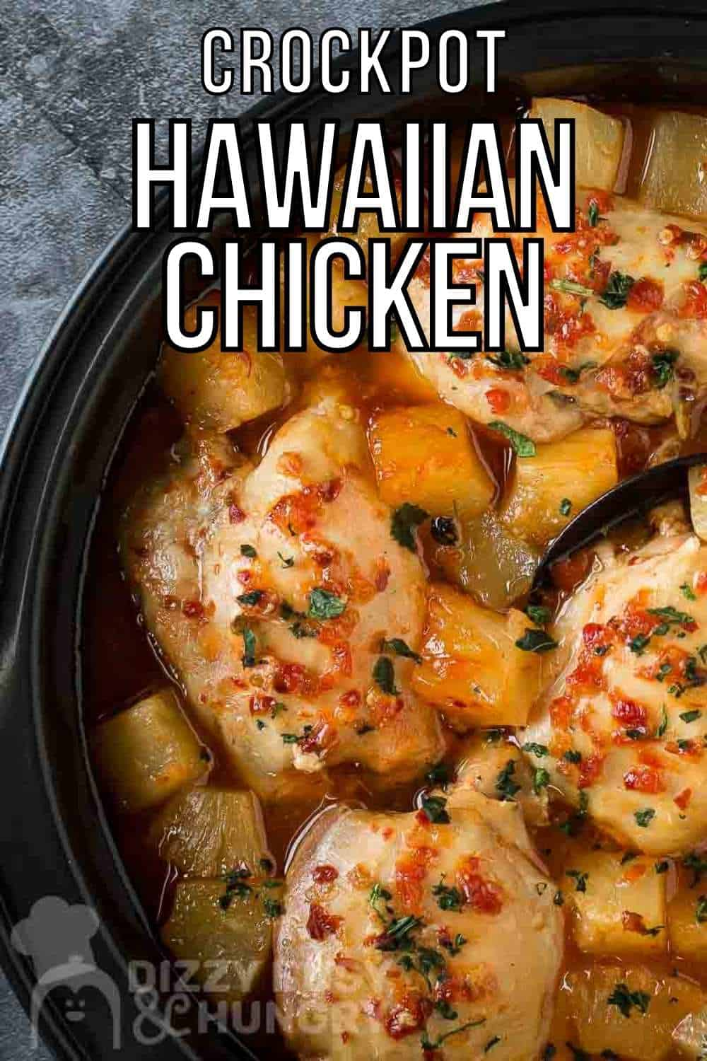 Overhead close up shot of Hawaiian chicken in the crockpot with a black spoon on a grey marble counter.