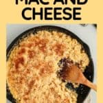 Overhead shot of Mac and cheese in a skillet with a portion taken out and a wooden serving spoon on the side.